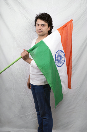 young indian male model in white tshirt holding indian flag Stock Photo