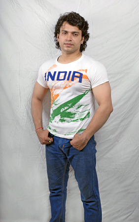 indian male model in white tri color tshirt and blue jeans photo