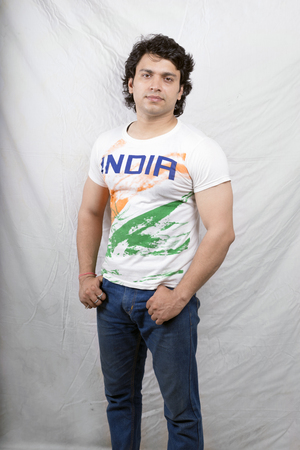indian fitness model wearing white tshirt and blue jeans photo