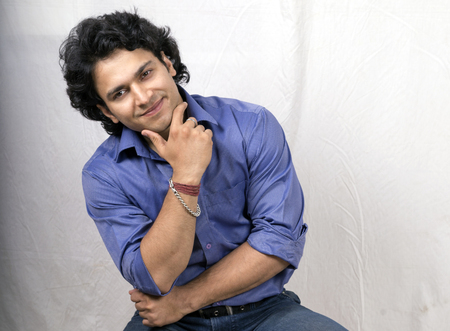 indian male model smiling pose in blue shirt Stock Photo