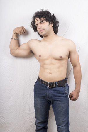Young Indian male bodybuilder posing biceps