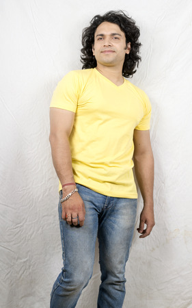 Indian male model wearing yellow tshirt and blue jeans side pose