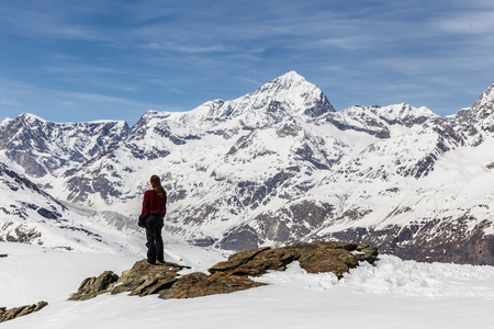 topcoat: A woman standing on the snow in the background of Matterhorn and snow mountain.