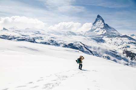 adventure travel: A man standing on the snow looking at the background of Matterhorn.