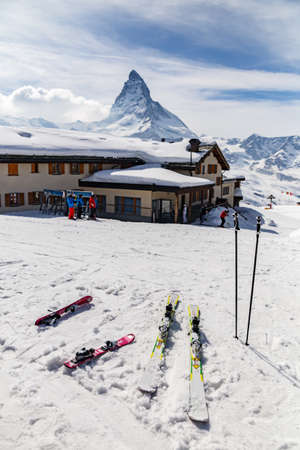 swiss alps: Ski equipment place on snow ground with the background of restaurant and Matterhorn