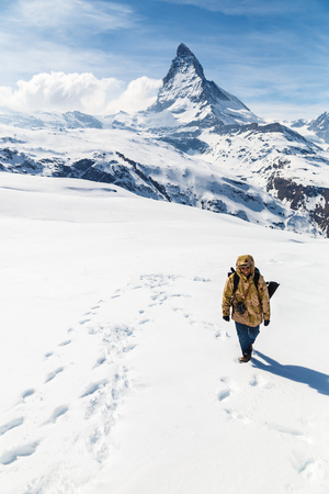 mountain top: A man in camouflage winter coat walking on the snow with the background of Matterhorn. Stock Photo
