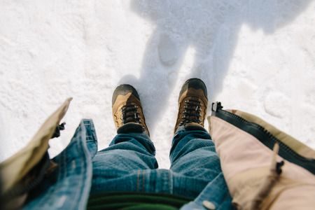 first day: First-person view. Man bend down the head looking for his boots standing on snow