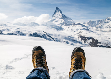 Mens legs in the trekking boots lying on the snow with the background of Matterhorn, Switzerland.
