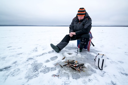 Ice fishing and happy fisherman with pike