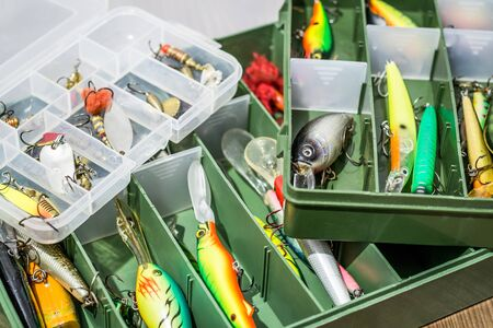 Spoon baits, lures, tackles and wobblers in box for catching or fishing a predatory fish on deck wood background