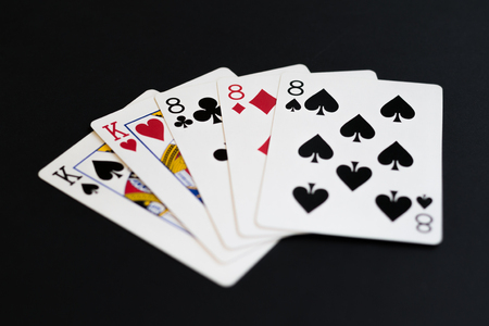 Full house in poker cards game on a black background. Stock Photo