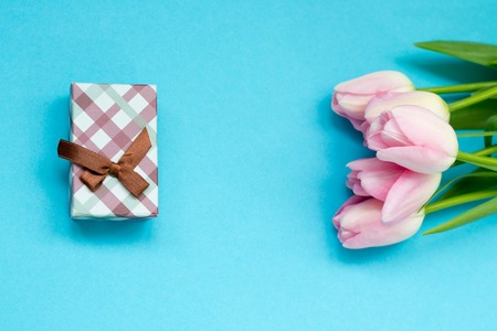 Pink tulips on the blue background with gift box. Flat lay, top view. Valentines background. Stock Photo