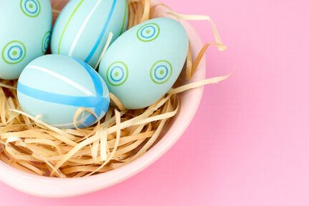 Happy easter composition. Nest with blue pained easter eggs. Texture pink background. Flat lay, top view and copyspace.