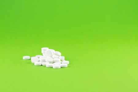 Close up white pills on green background with copy space. Focus on foreground, soft bokeh. Pharmacy drugstore concept.