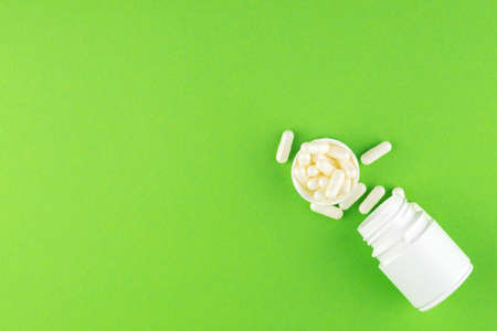 Close up white pill bottle with spilled out pills and capsules in cap on green background with copy space. Focus on foreground, soft bokeh. Pharmacy drugstore concept. Top view.