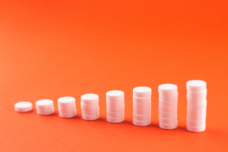 Close up pyramid concept of white pills on orange background with copy space. Stock Photo