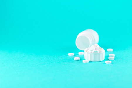 Close up white pill bottle with spilled out pills and capsules in cap on turquoise background with copy space.