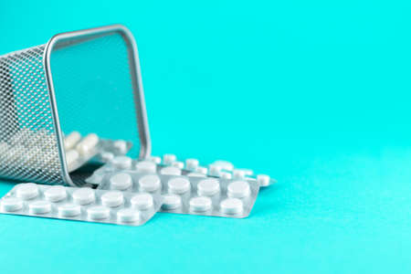 Trash bin with packs of white capsules and pills packed in blisters with copy space on turquoise background. Imagens
