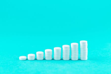 Close up pyramid concept of white pills on turquoise background with copy space. Stock Photo