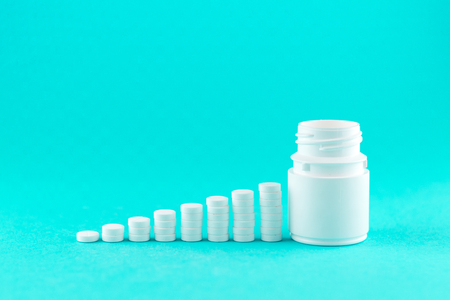 Close up pyramid concept of white pills and bottle on turquoise background with copy space.
