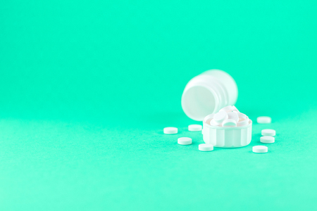 Close up white pill bottle with spilled out pills and capsules in cap on aquamarine background with copy space. Focus on foreground, soft bokeh. Pharmacy drugstore concept.