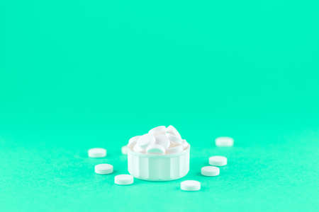 Close up white pills and capsules in cap on aquamarine background with copy space. Focus on foreground, soft bokeh. Pharmacy drugstore concept. Stock Photo