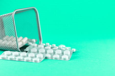 Trash bin with packs of white capsules and pills packed in blisters with copy space on aquamarine background. Focus on foreground, soft bokeh.