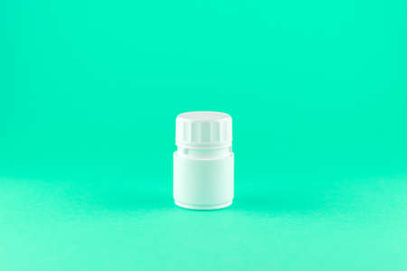 Close up white pill bottle on aquamarine background with copy space. Focus on foreground, soft bokeh. Pharmacy drugstore concept. Stock Photo