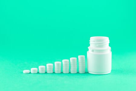 Close up pyramid concept of white pills and bottle on aquamarine background with copy space. Focus on foreground, soft bokeh. Pharmacy drugstore concept. Stock Photo