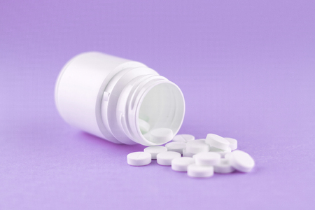 Close up white pill bottle with spilled out pills on purple background with copy space. Focus on foreground, soft bokeh. Pharmacy drugstore concept.