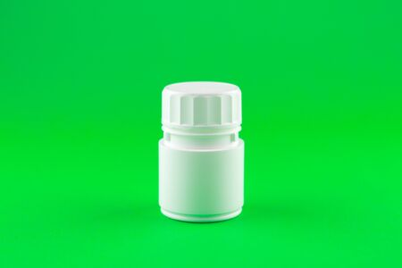 Close up white pill bottle on lime green background with copy space. Focus on foreground, soft bokeh. Pharmacy drugstore concept. Stock Photo
