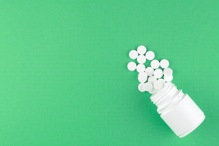 Close up white pill bottle with spilled out pills on jade green background with copy space. Focus on foreground, soft bokeh. Pharmacy drugstore concept. Top view.