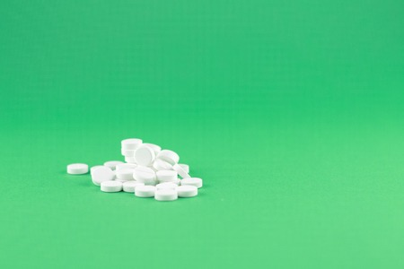Close up white pills on jade green background with copy space. Focus on foreground, soft bokeh. Pharmacy drugstore concept.