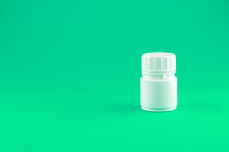 Close up white pill bottle on shamrock green background with copy space. Focus on foreground, soft bokeh. Pharmacy drugstore concept.