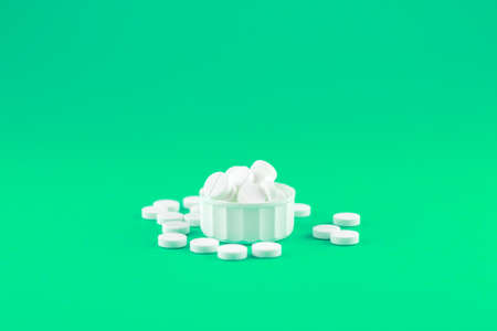 Close up white pills and capsules in cap on shamrock green background with copy space. Focus on foreground, soft bokeh. Pharmacy drugstore concept.