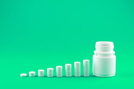 Close up pyramid concept of white pills and bottle on shamrock green background with copy space. Focus on foreground, soft bokeh. Pharmacy drugstore concept.