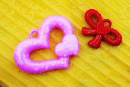 Pink and red heart on yellow banana leaf background Stock Photo