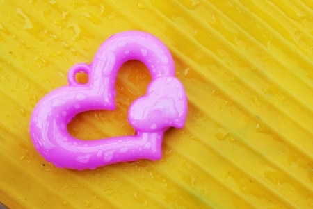 Pink heart on yellow banana leaf  background