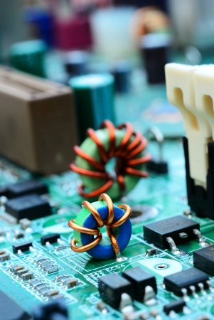 Close up of an mini electronic printed ferrite ring with computer mainboard background photo