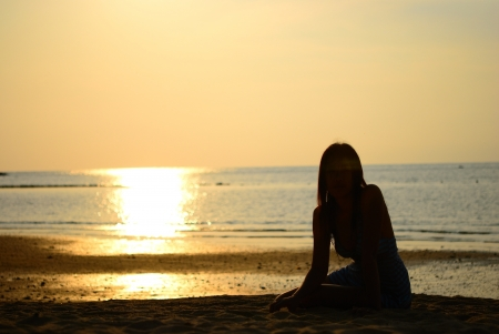Silhouette of Asian woman sit on the beach Stock Photo