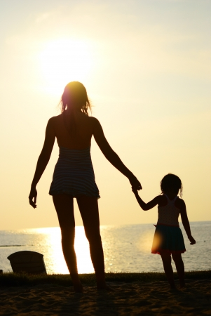 Silhouette of mom and daughter walk to the sea Stock Photo