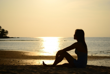Silhouette of Thai woman take a rest on the beach in the evening photo