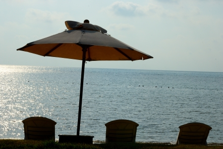 Silhouette of umbrella on the beach with beach bed