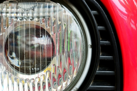 headlamp: Old headlamp of red vehicle with the scratch
