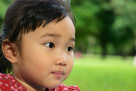 The kid look to something in the gree garden Stock Photo