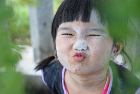 Cheeky face from Thai kid with powder on her face photo
