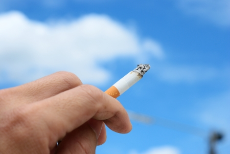 Smoker hand on the blue sky background photo