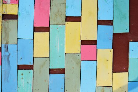 Colorful wood separated on plywood wall background Stock Photo