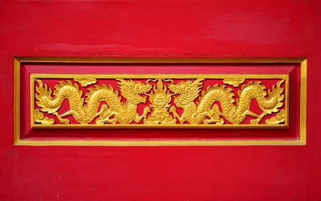A coupple golden dragon on the red wall of Chinese temple in Thailand photo
