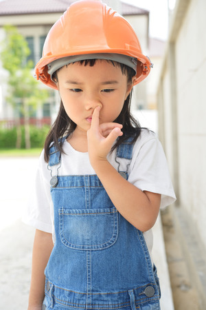 nose picking: Little engineer make a nose picking and look boring after inspected the building Stock Photo
